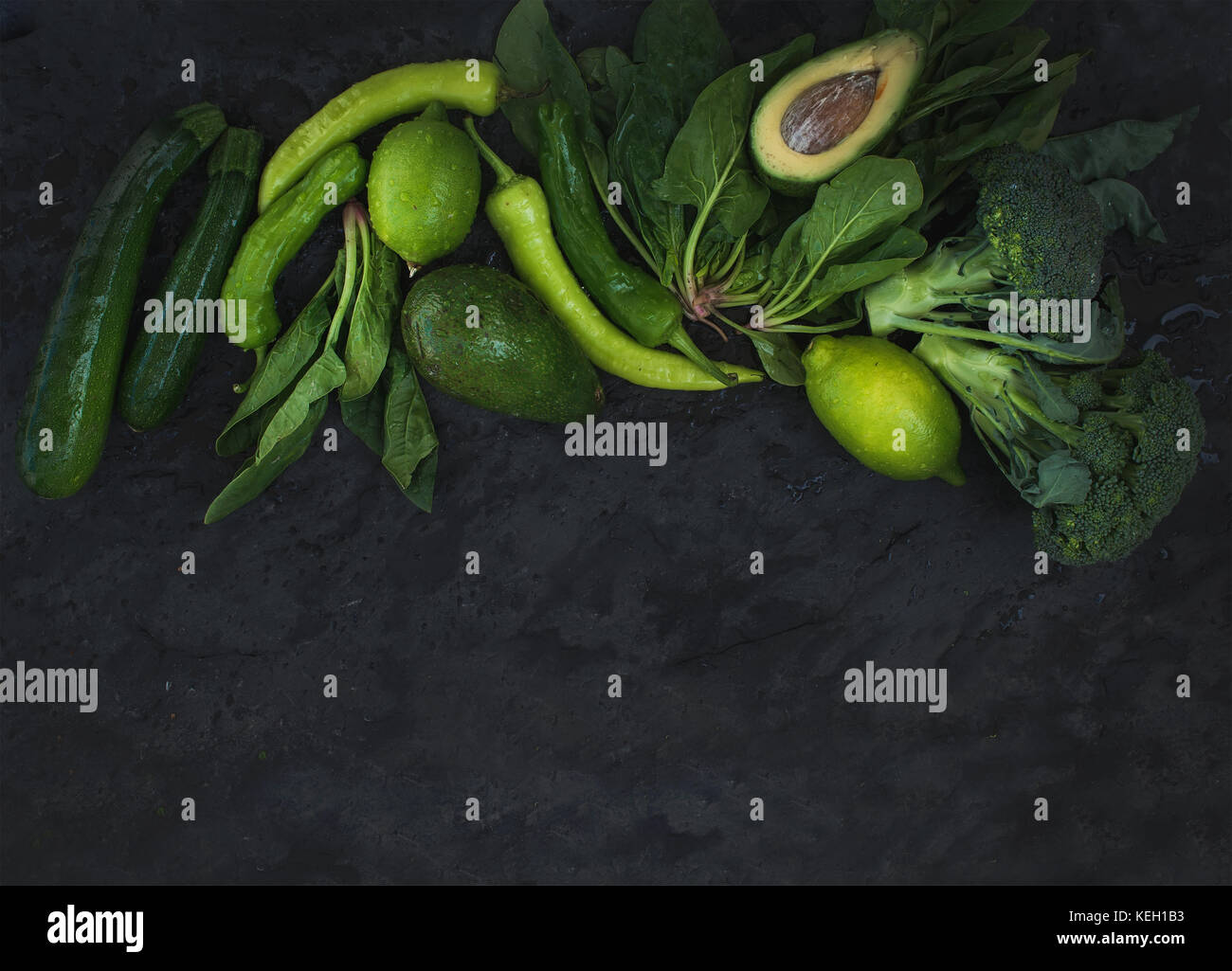 Raw green vegetables set. Broccoli, avocado, pepper, lime on dark stone background, top view, copy space - Stock Image