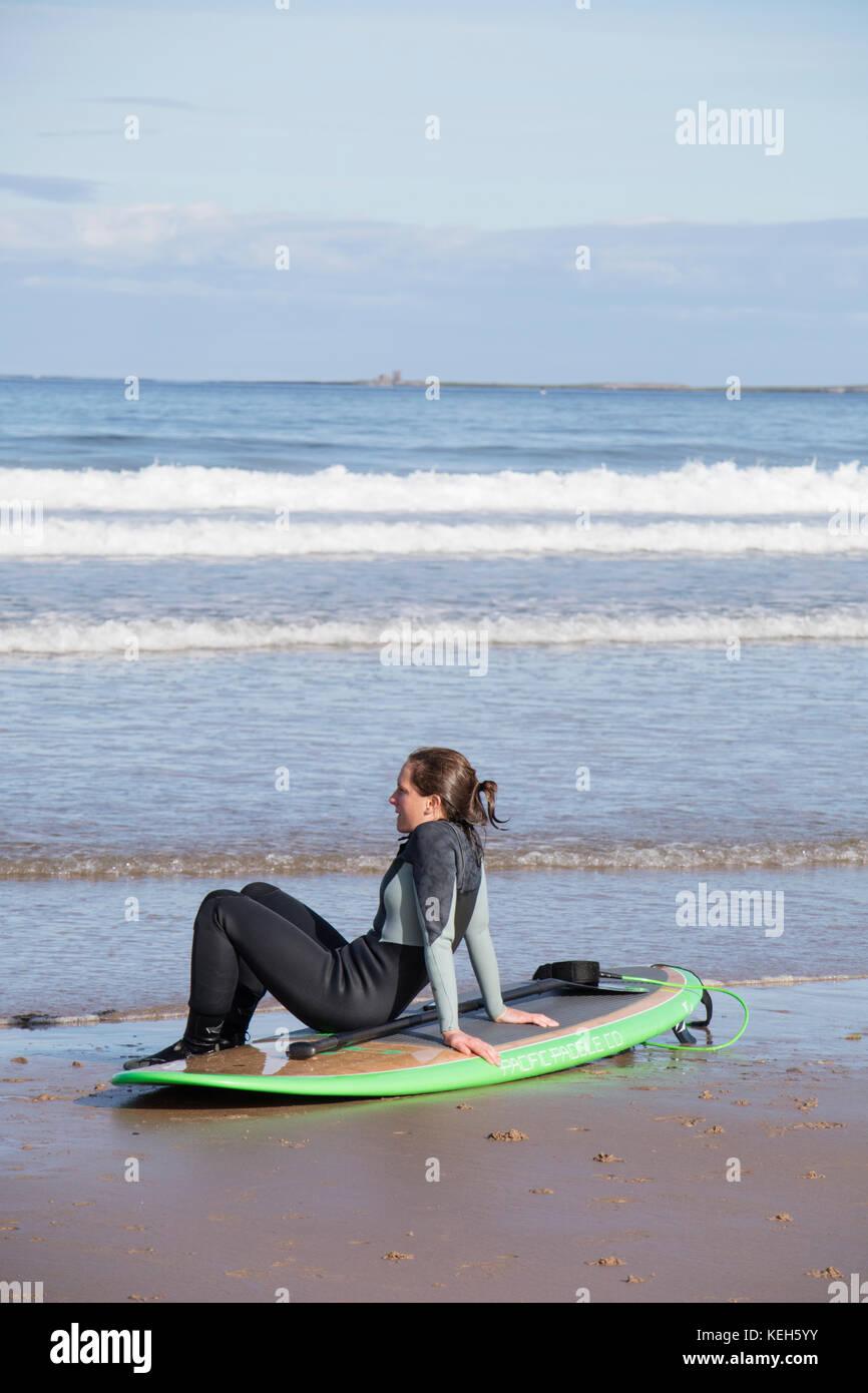 Surfing on Bamburgh beach, Northumberland, England, UK - Stock Image