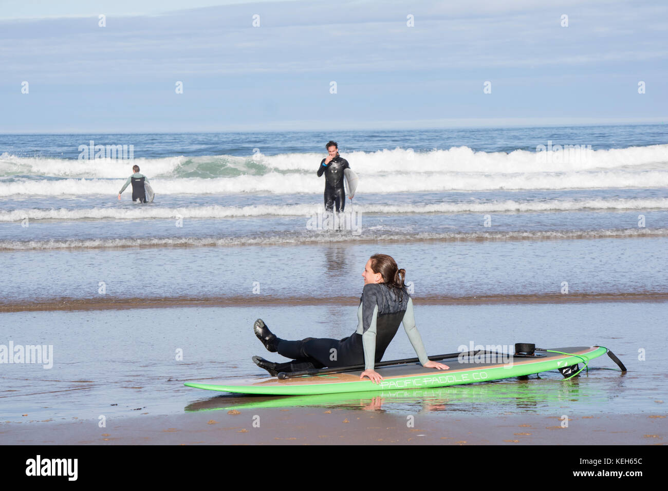 Surfing on Bamburgh beach, Northumberland, England, UK Stock Photo