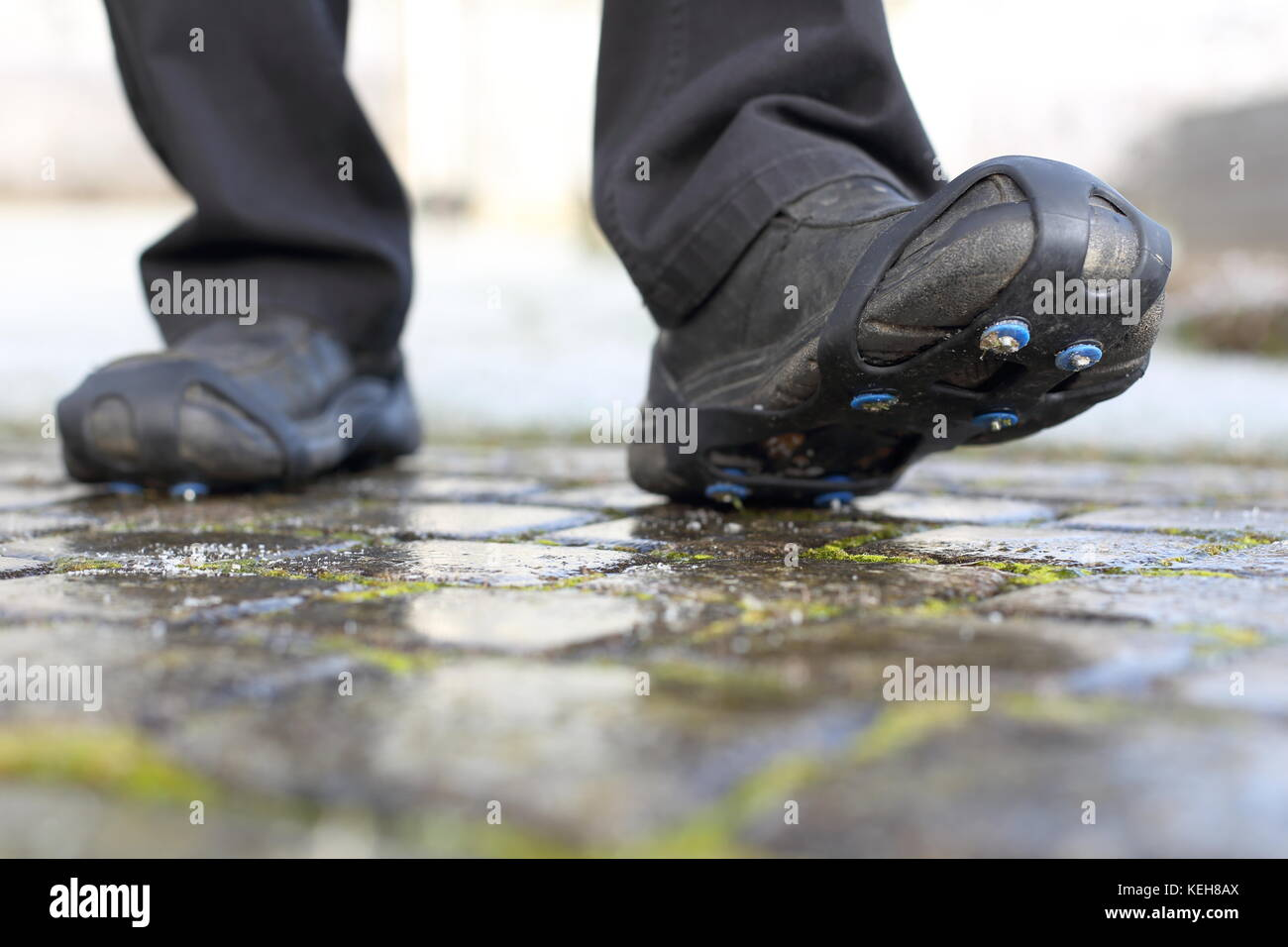 Pair of Shoe spikes snow chains an a icy road in winter - Stock Image