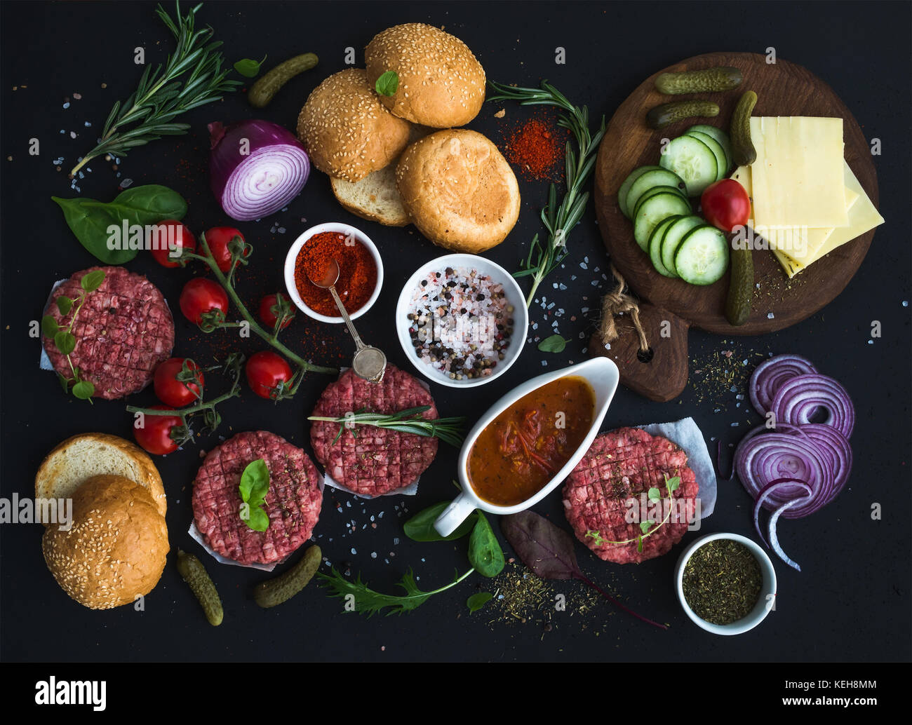 Ingredients for cooking burgers. Raw ground beef meat cutlets, buns, red onion, cherry tomatoes, greens, pickles, - Stock Image