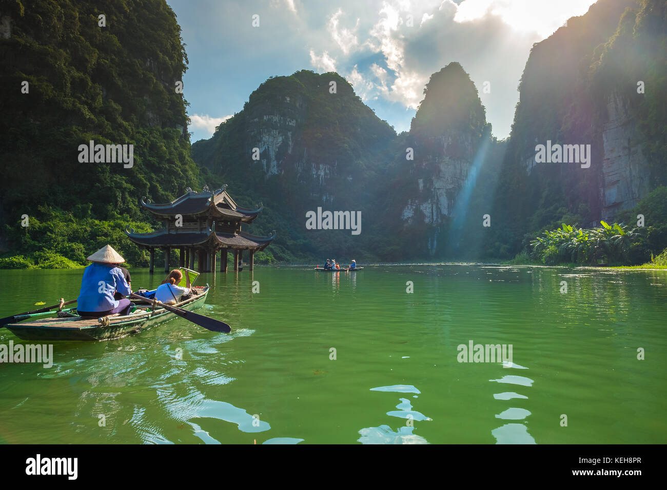 Sep 18, 2017 Foreign tourists ride local boat in Trang An landscape complex, Ninh Binh, Hanoi, Vietnam - Stock Image