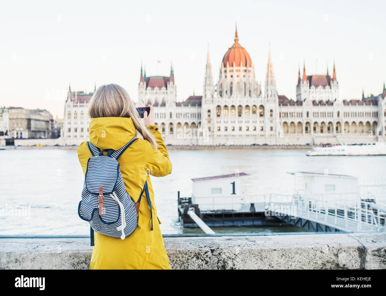 Young blondy woman tourist making photos of Parliament historic building from Danube side with her phone in Budapest, - Stock Image