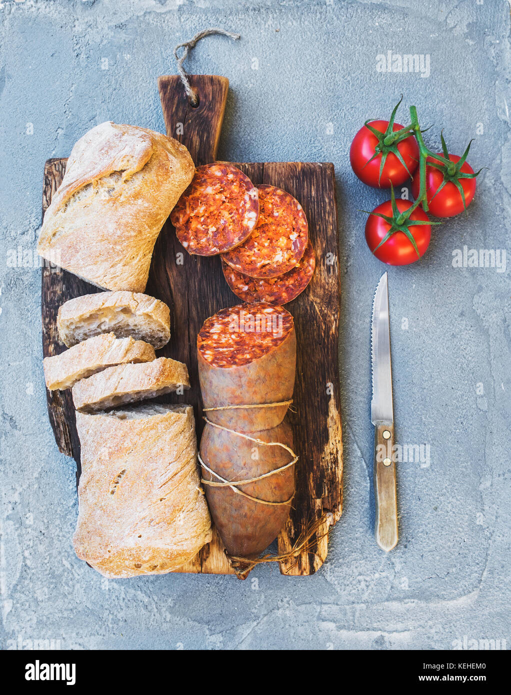 Wine snack set. Hungarian mangalica pork salami sausage, rustic bread and fresh tomatoes on dark wooden board over - Stock Image