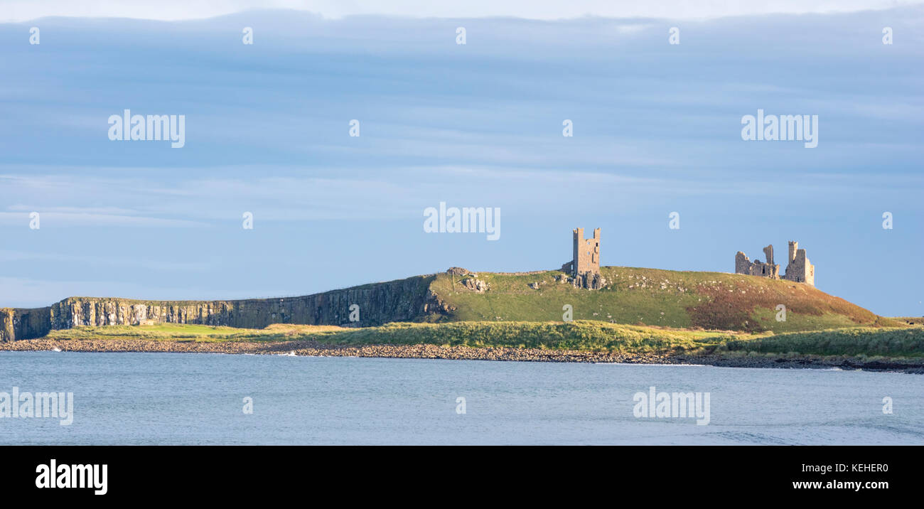 Evening light over Dunstanburgh Castle, Northumberland, England, UK - Stock Image