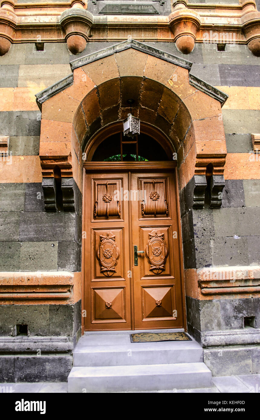 Stone arched visor with a console over the wooden door on the facade of the old building - Stock Image