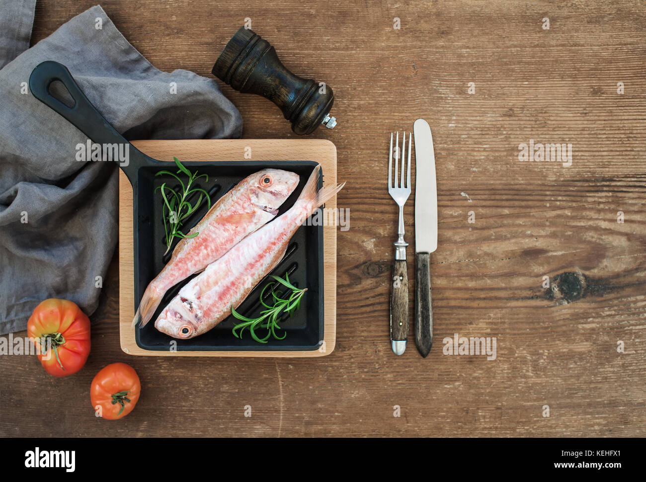 Raw uncooked Red Mullet fish in a cooking pan with rosemary, lemon and garlic over rustic wooden background, top - Stock Image
