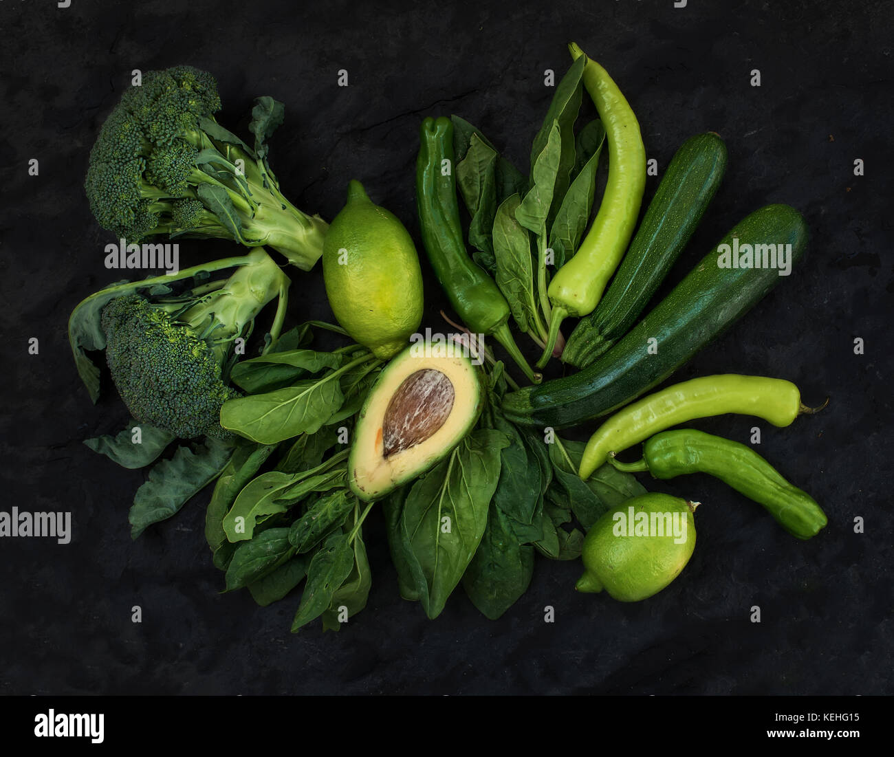 Raw green vegetables set. Broccoli, avocado, pepper, spinach, zuccini and lime on  dark stone background, top view - Stock Image