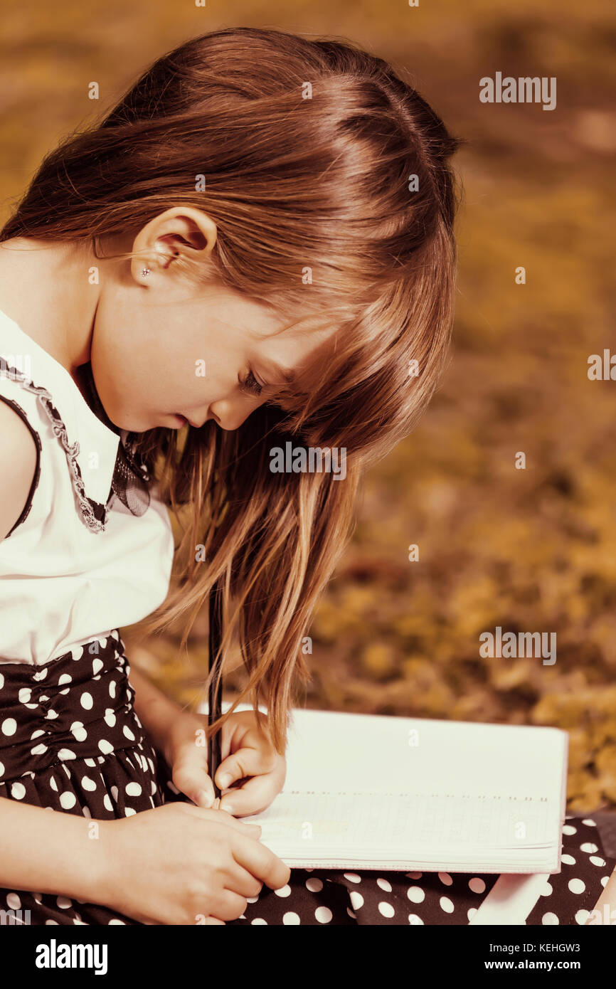 Little cute little girl draws and writes in her notebook. She is very inspired when in nature, outdoors - Stock Image