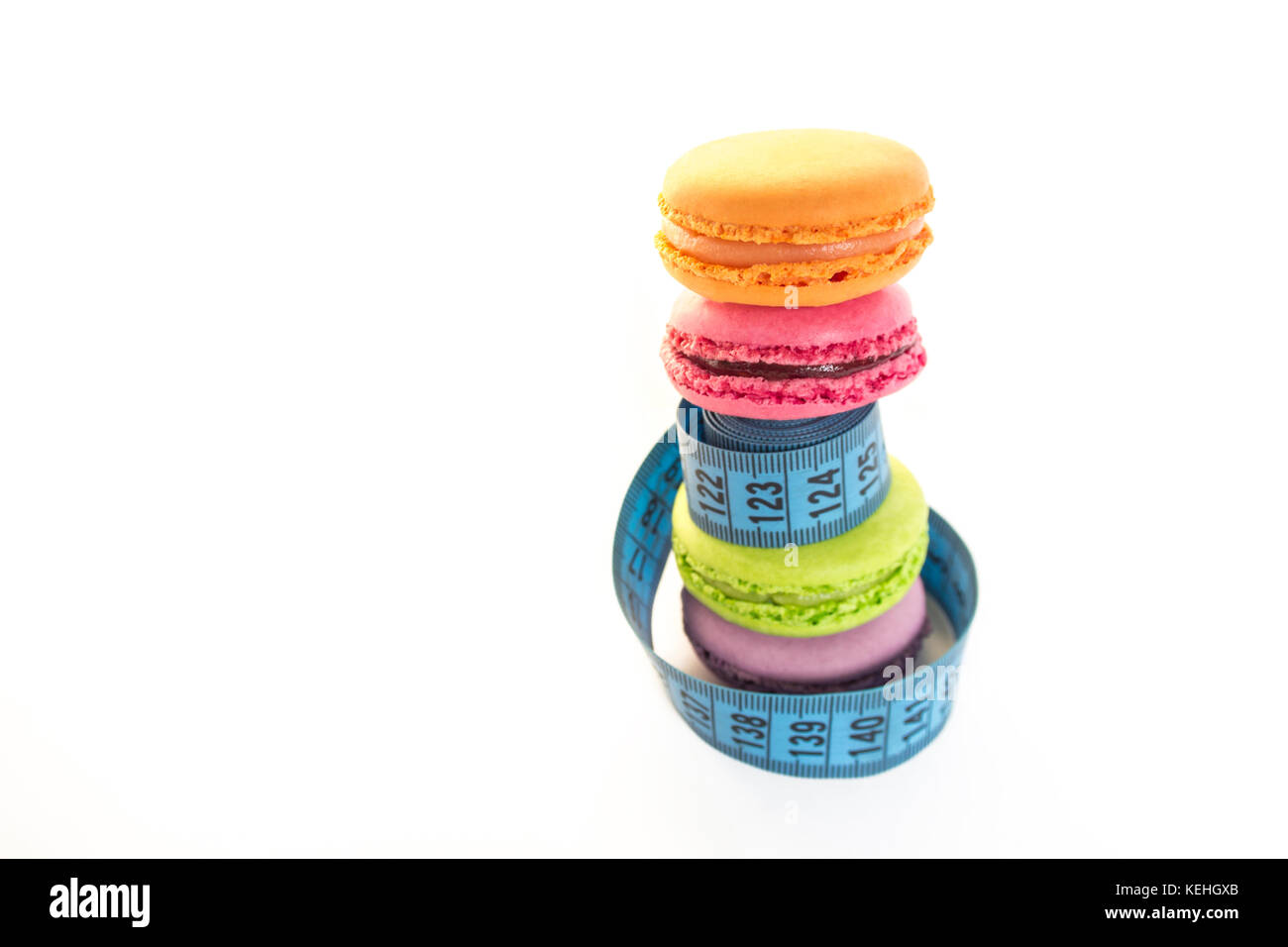 Colorful macaroons and blue meter tape, concept of healthy eating and nutrition - Stock Image