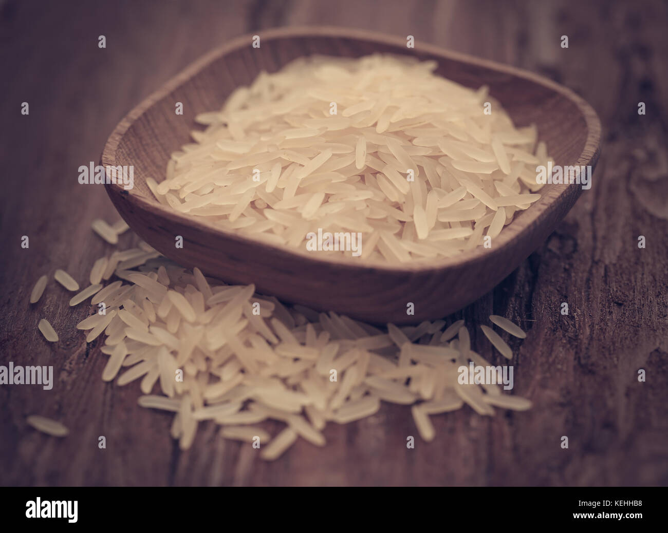 Basmati rice in a bowl on wooden surface - Stock Image