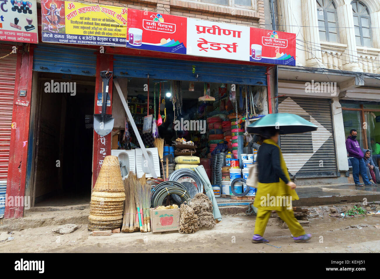 Female pedestrian with an umbrella passing by a hardware store in Kathmandu, Nepal. - Stock Image