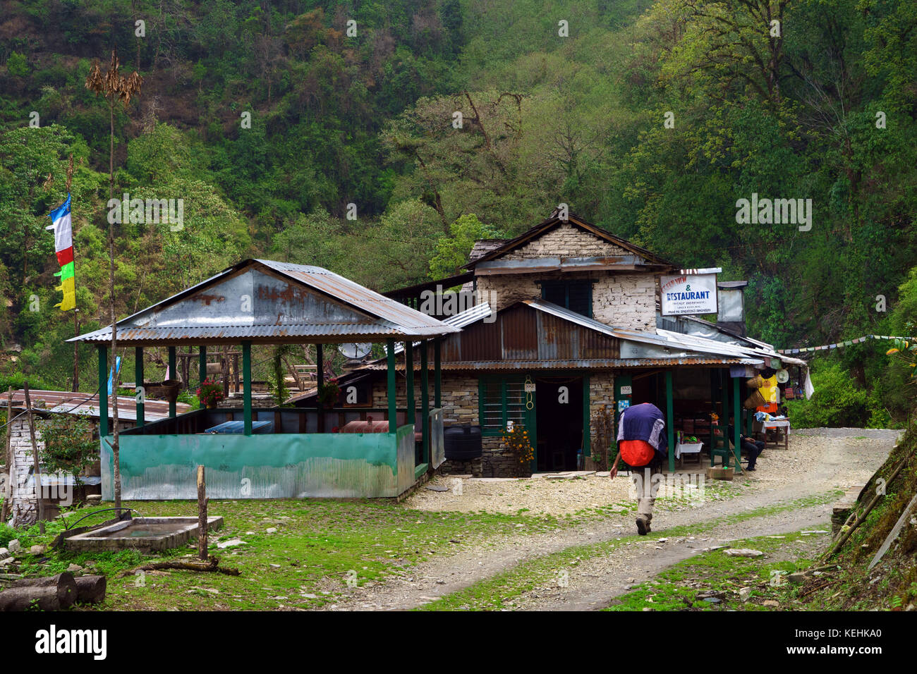 Trekker passing a guesthouse near Bhichuk on the Poon Hill trek, Nepal. - Stock Image