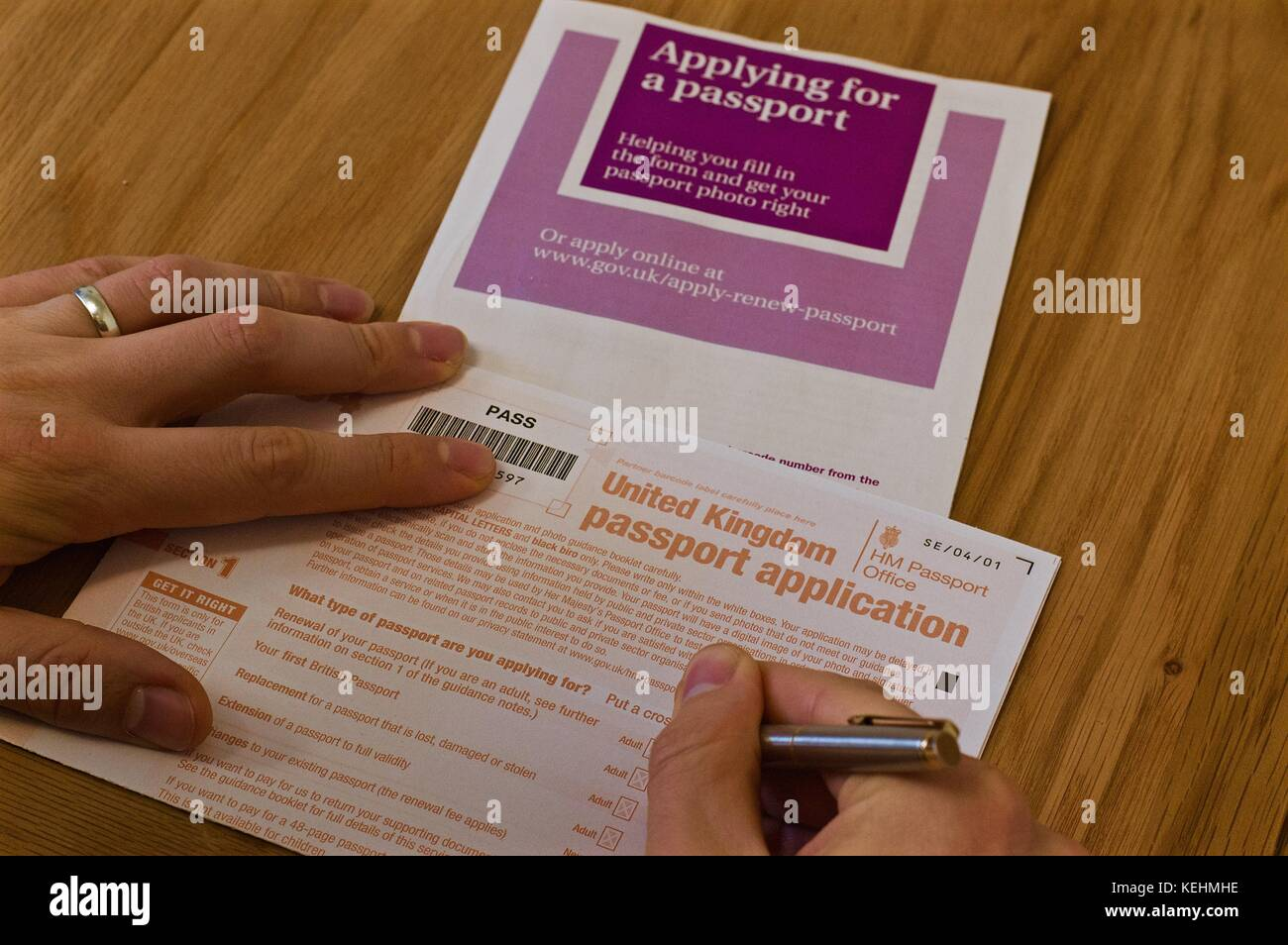 Passport application form stock photos passport application form view of mans hands filling out uk passport application form on table with instructional booklet falaconquin