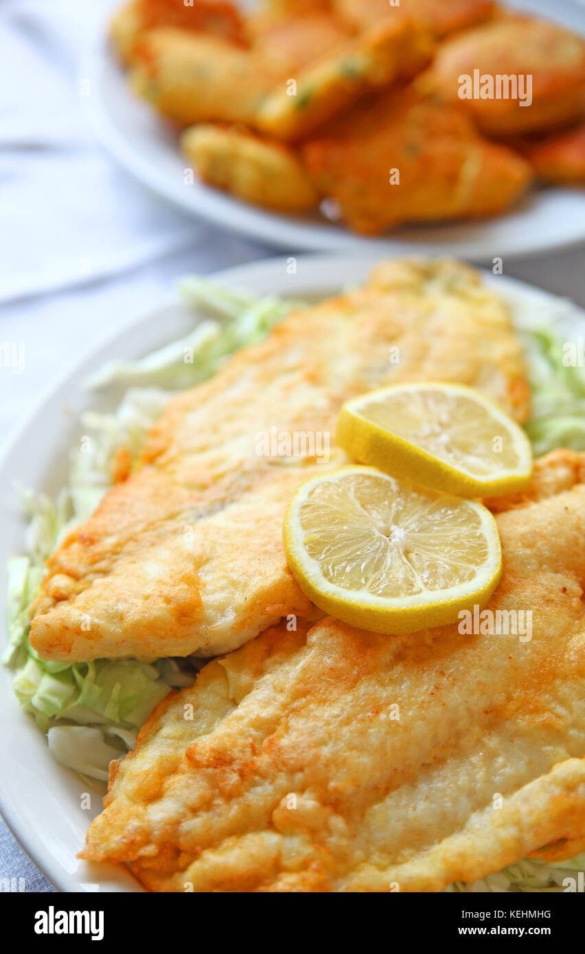 Battered and deep-fried catfish fillets on shredded cabbage with hushpuppies in the background - Stock Image