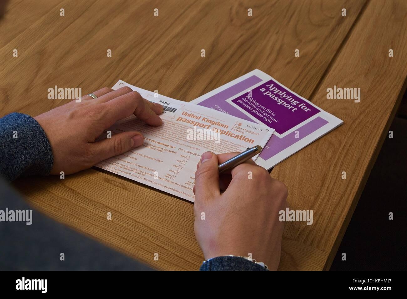 Uk passport application stock photos uk passport application stock view of mans hands filling out uk passport application form on table with instructional booklet falaconquin