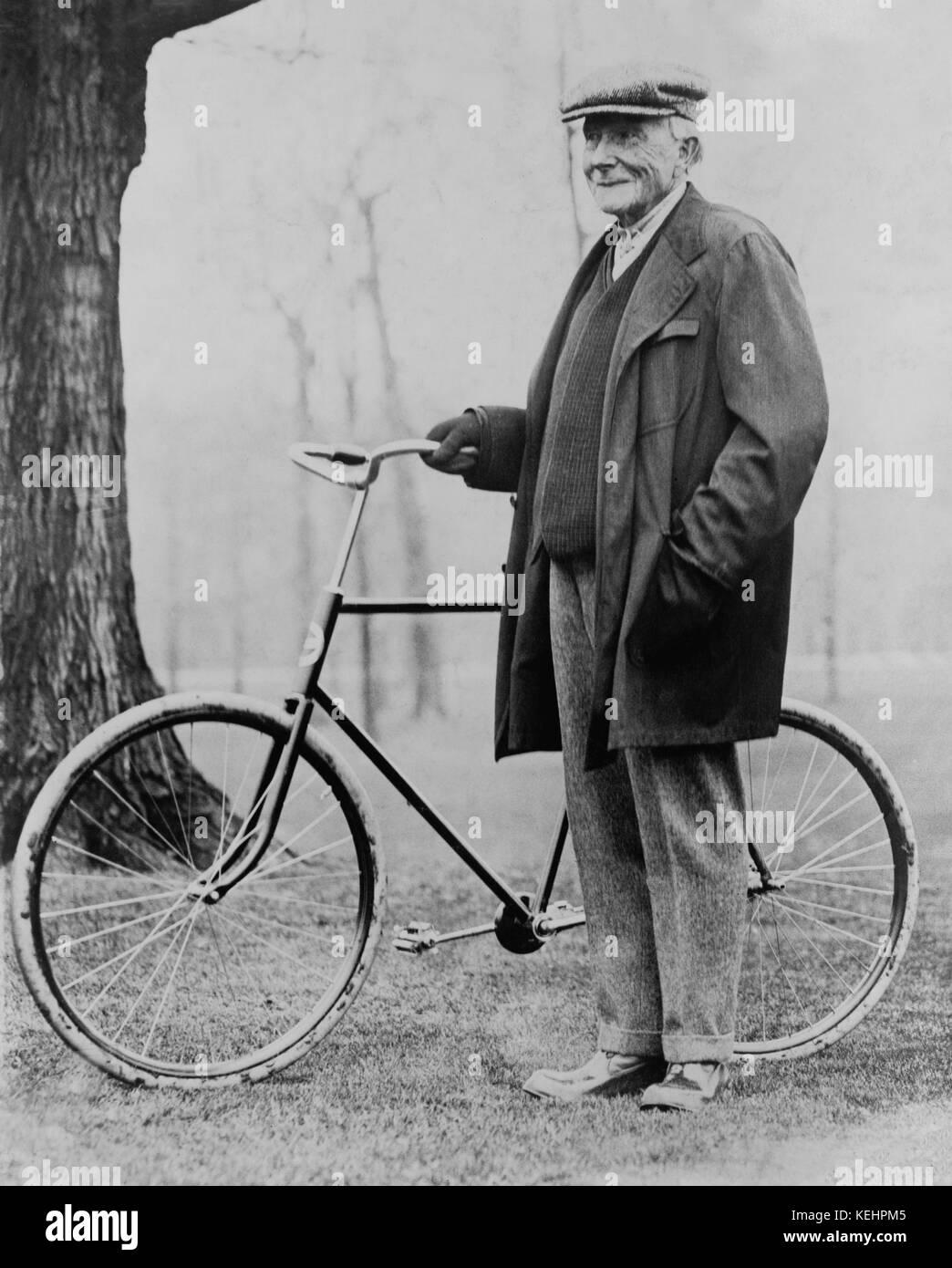 John D. Rockefeller (1839-1937),Portrait standing with Bicycle,1913 - Stock Image