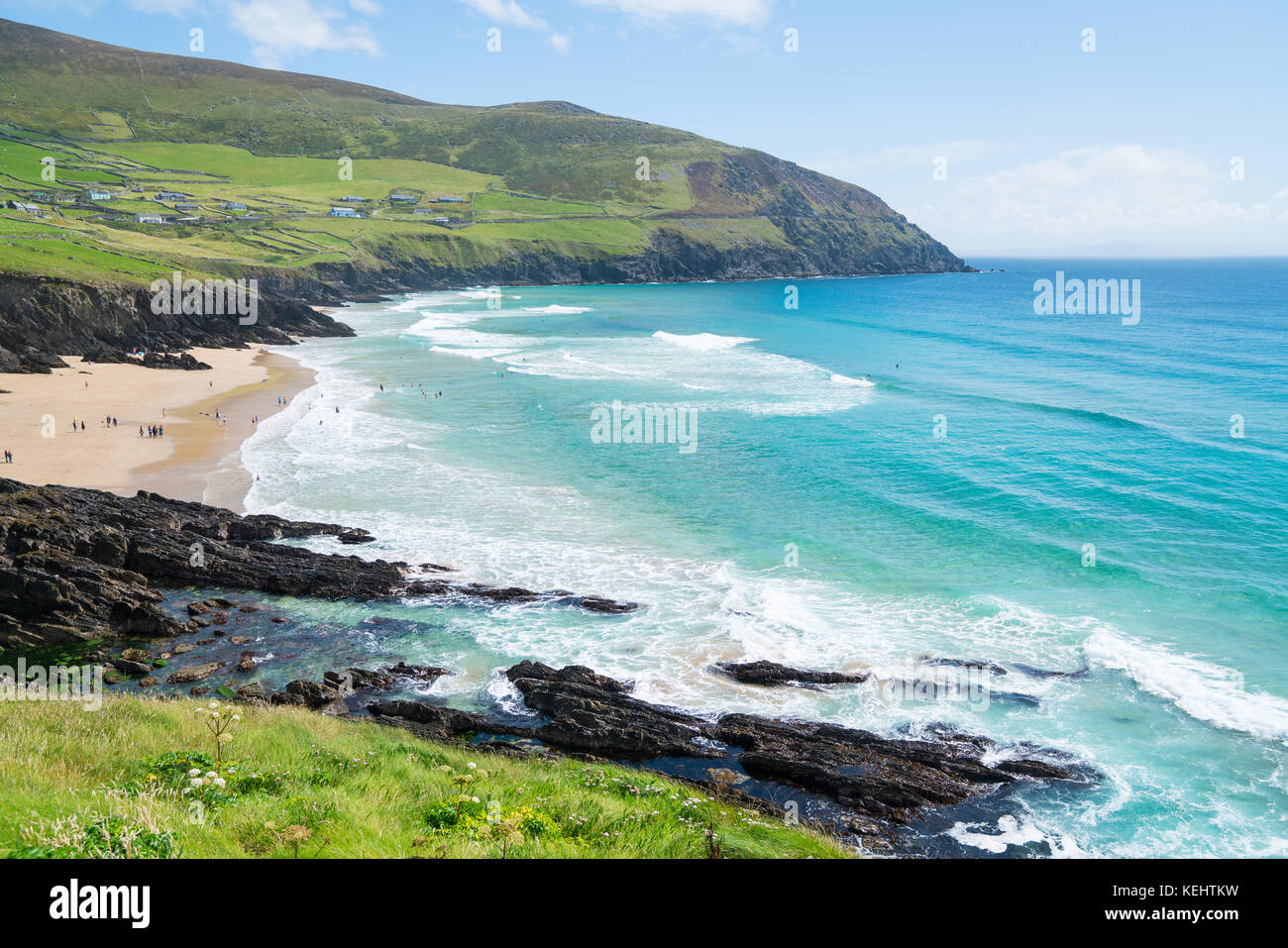 COUNTY KERRY, IRELAND- AUGUST 13, 2017; People enjoying an Irish summer day in distance on beach on west coast along - Stock Image