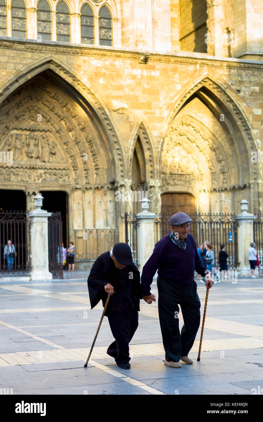 Elderly couple with walking sticks leave after Catholic Mass at Santa María de León Cathedral in Leon, - Stock Image