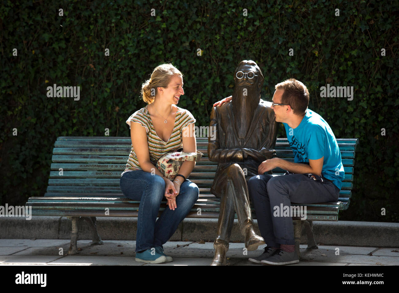 People sit on bench with bronze statue of Don Ramon Maria Del Valle-Inclan by sculptor Cesar Lombera in Alamada Stock Photo