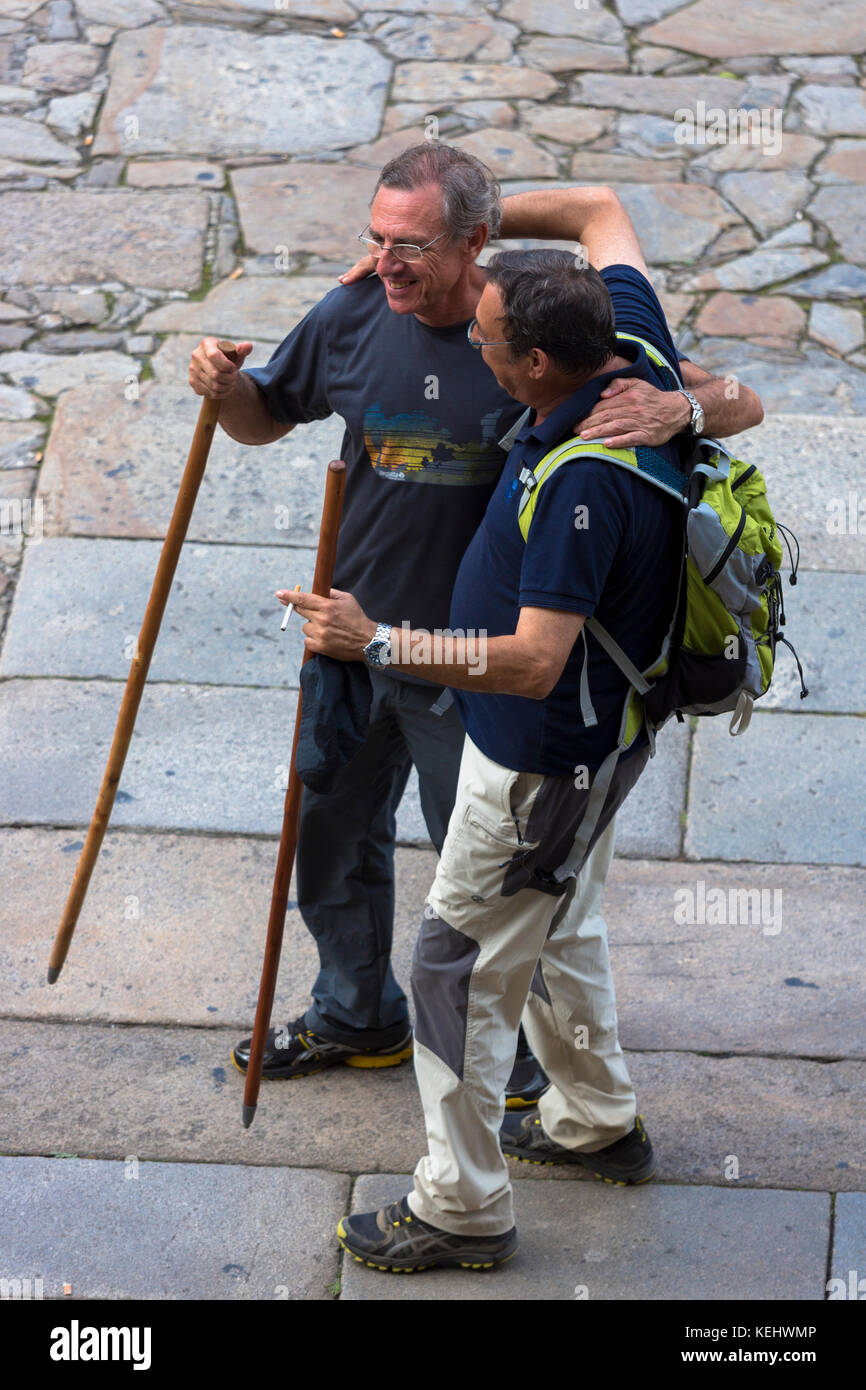 Pilgrims with walking poles end their Way of St James pilgrimage in Cathedral square of Santiago de Compostela, - Stock Image