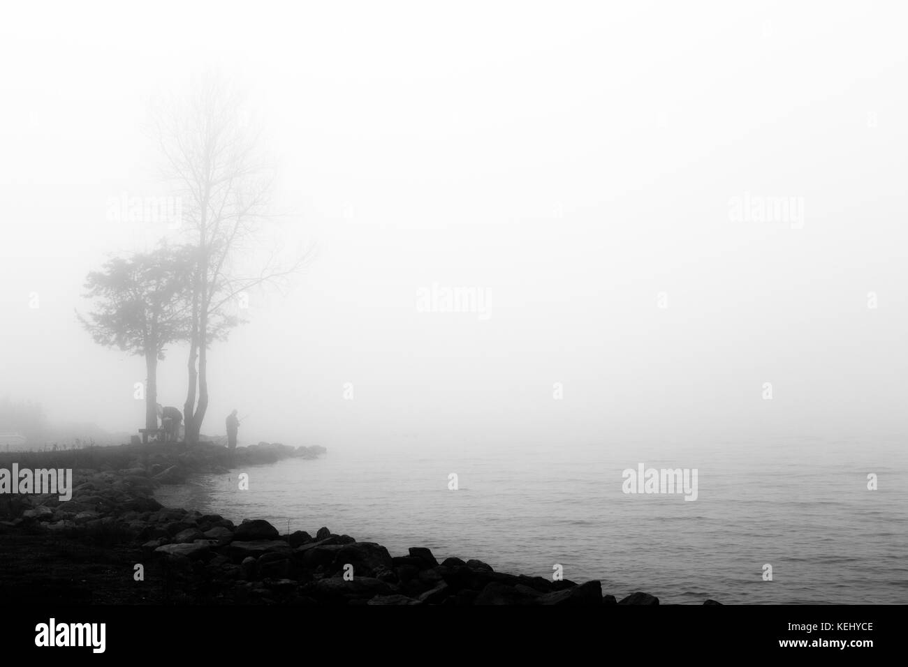 A lake hidden by fog, with rocks in the foreground and a fisherman and trees in the background - Stock Image