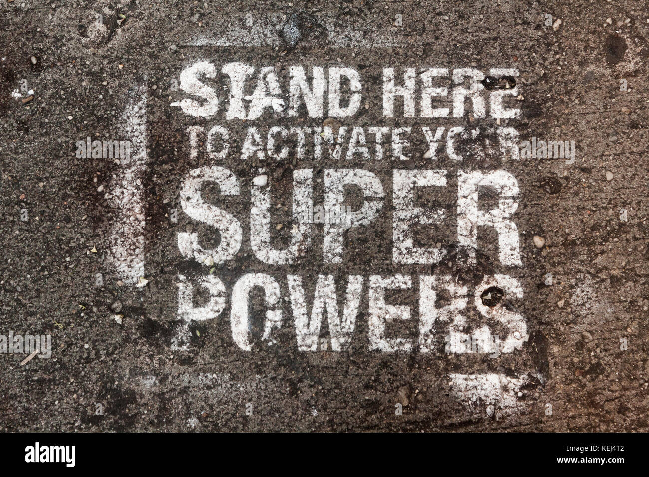 Stand Here to Activate Your Super Powers - spray-painted stencil on the sidewalk in NYC - Stock Image