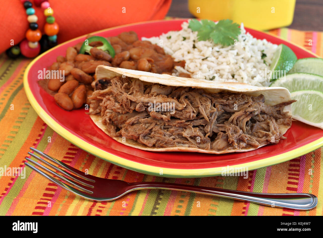 Pulled pork taco with a side of chili beans, basmati rice, and lime slices.  Selective focus on meat. - Stock Image