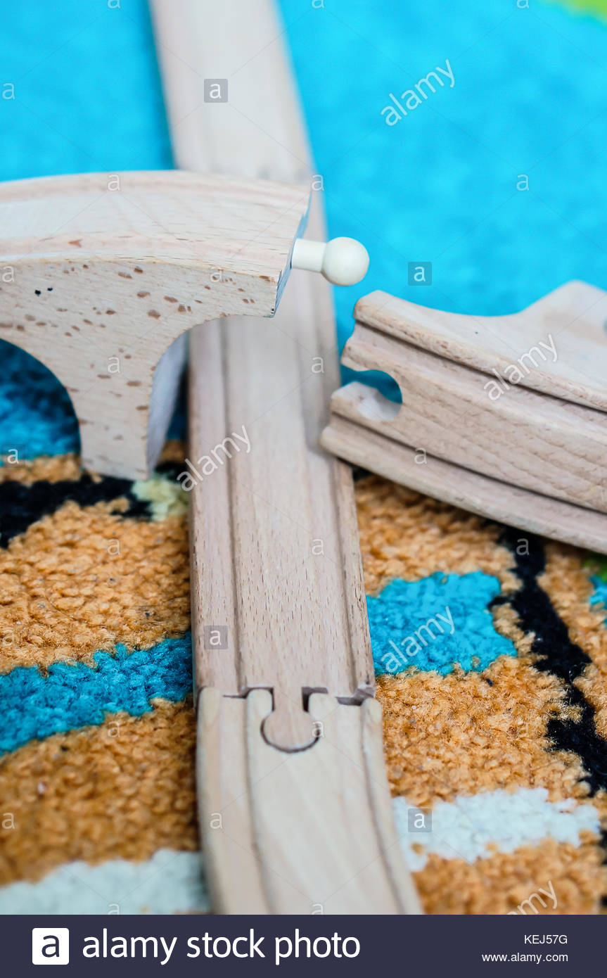 Wooden toy train track on a carpet in soft focus Stock Photo