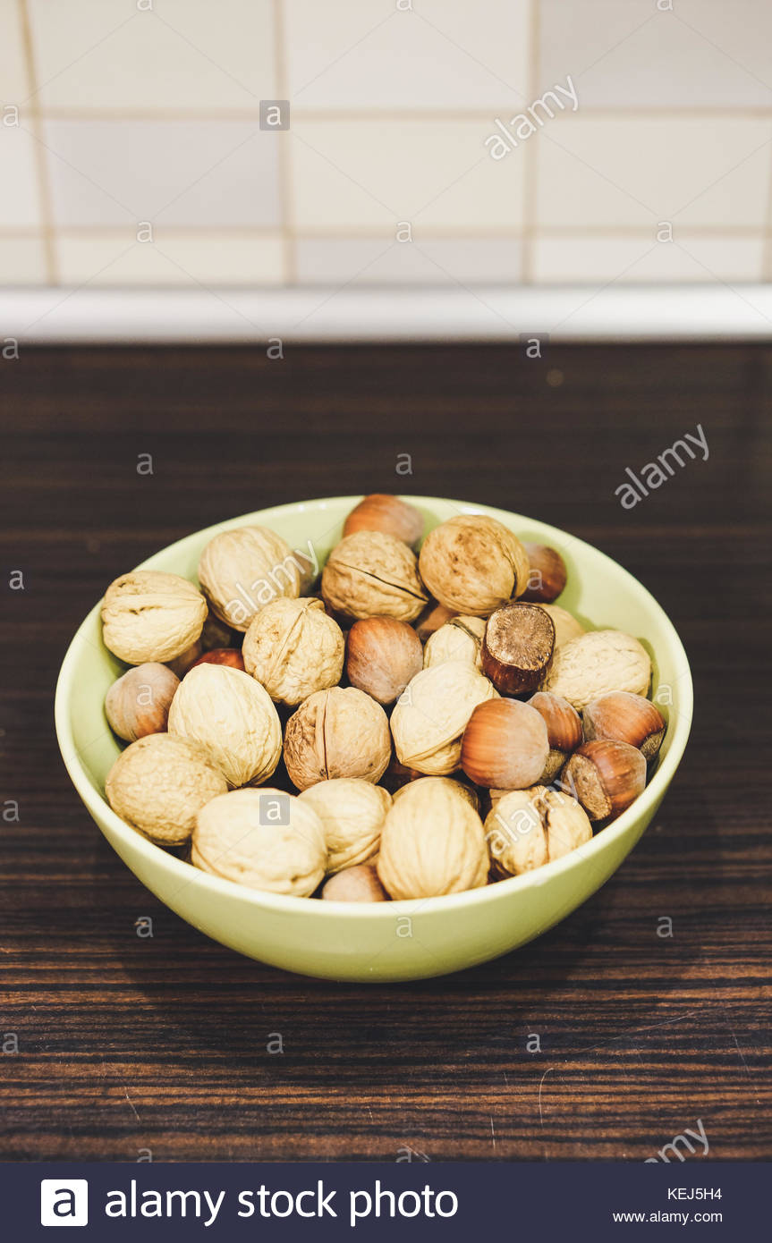 Whole hazelnuts and walnuts in a green bowl on wooden table in soft focus - Stock Image