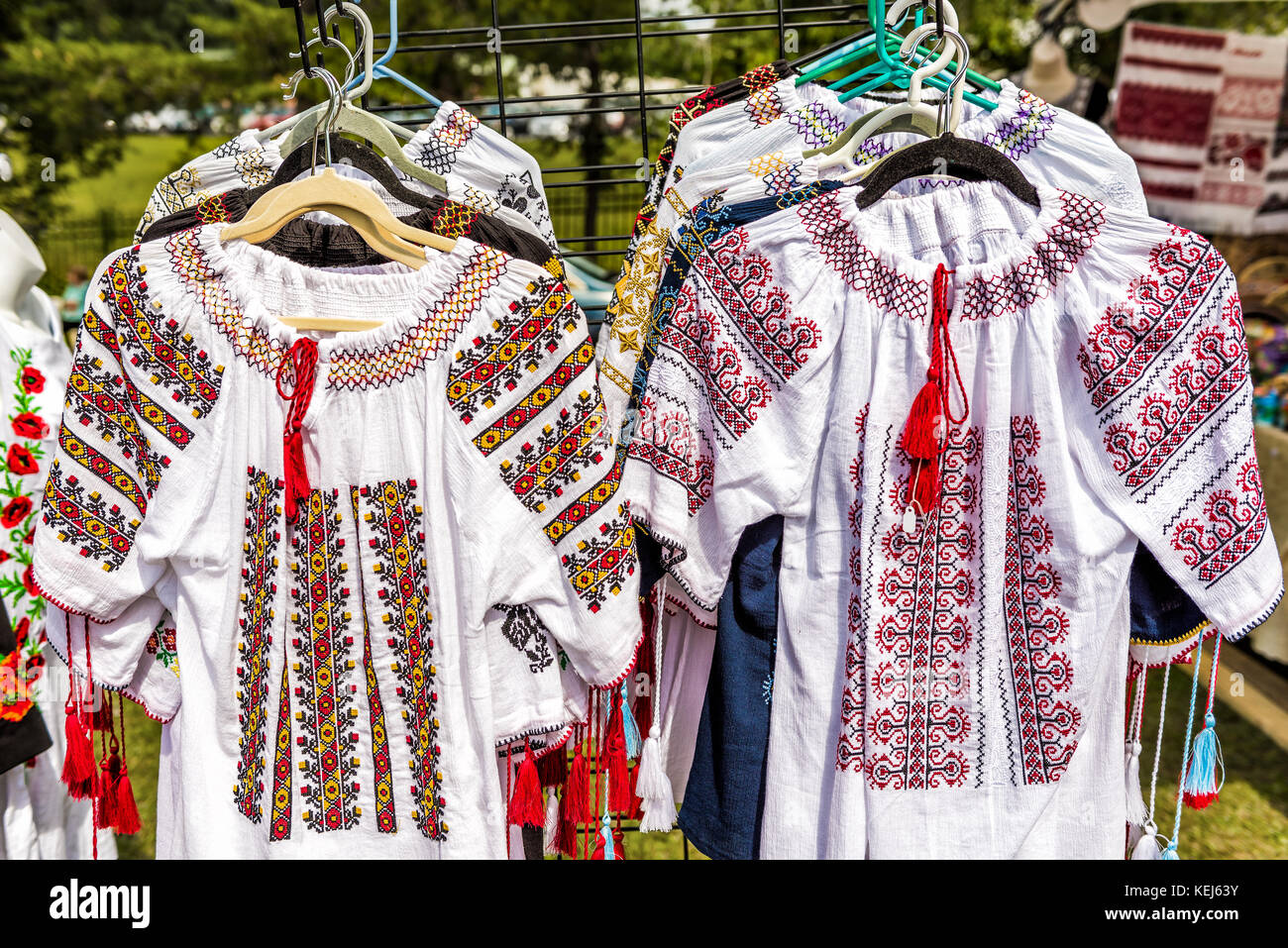 Display of embroidered Ukrainian slavic women traditional shirts embroidery clothing in outdoor flea market - Stock Image