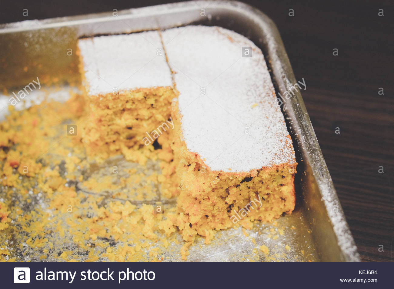 Cut parts of a carrot cake in a metal oven dish in soft focus - Stock Image