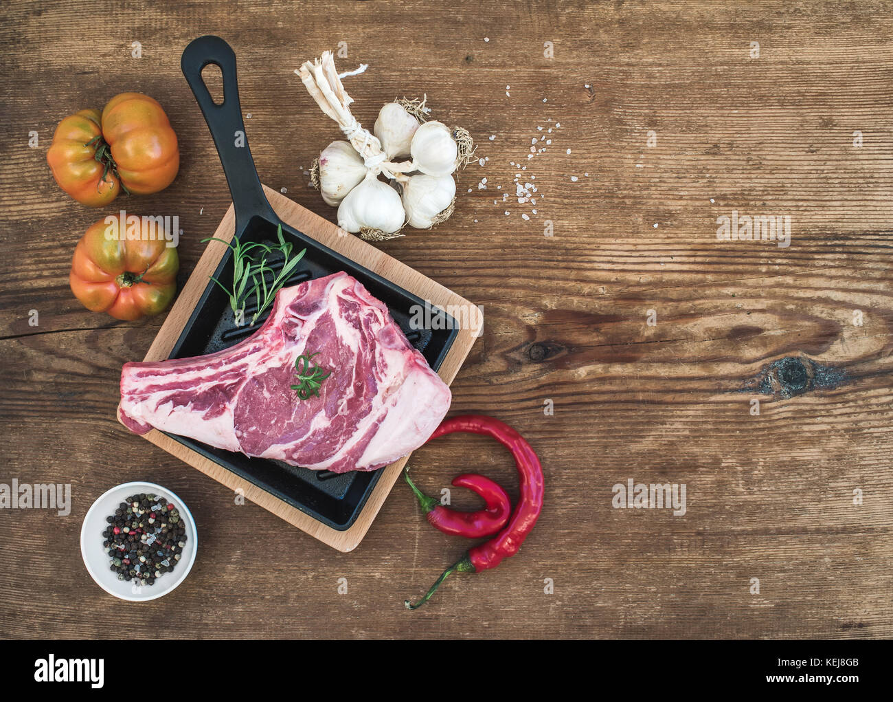 Raw fresh meat ribeye steak with pepper, salt, chili, garlic, spinach, heirloom tomatoes and rosemary in cooking - Stock Image