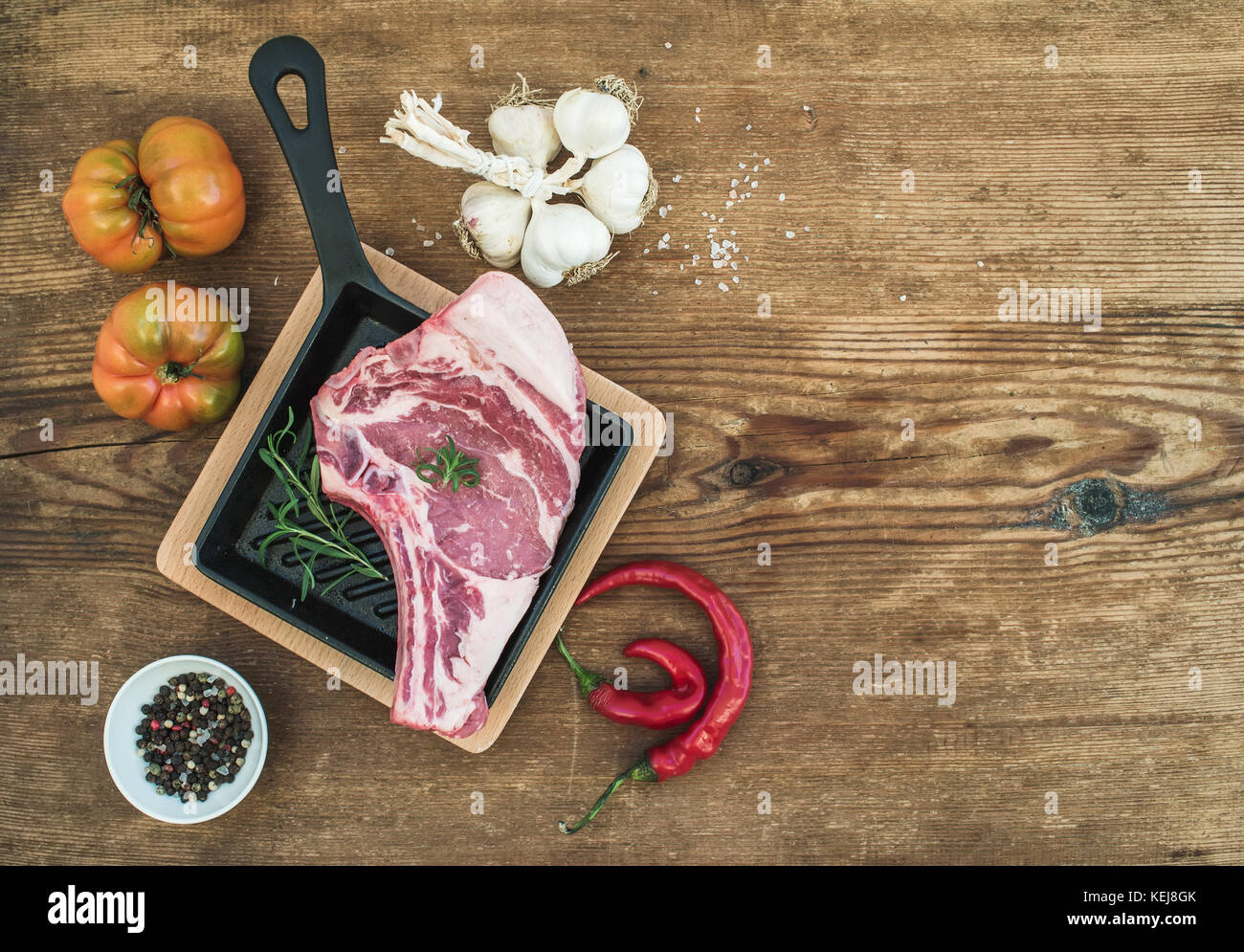 Raw fresh meat ribeye steak with pepper, salt, chili, garlic, heirloom tomatoes and rosemary in cooking pan over - Stock Image