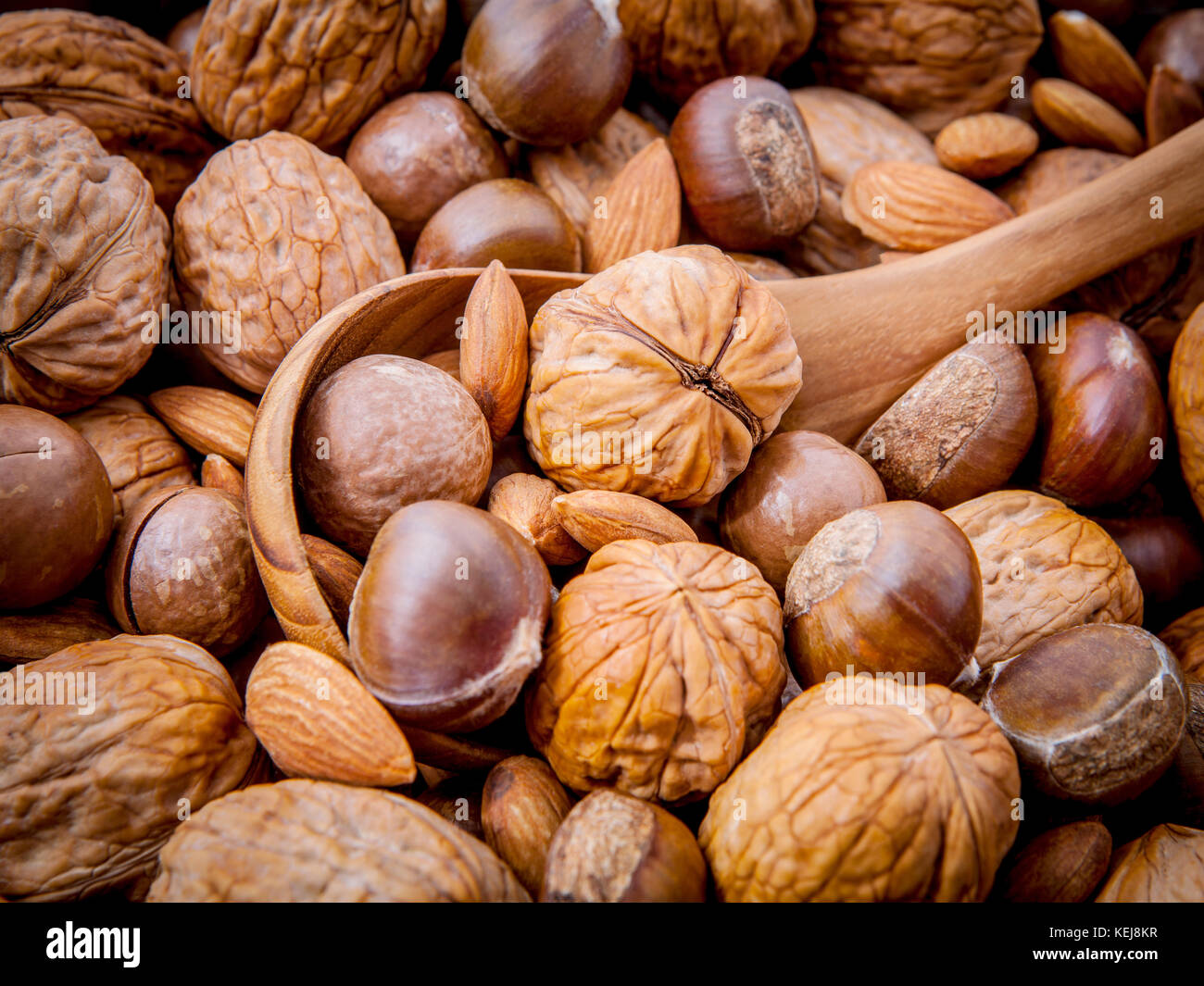 Background with different kinds of nuts  walnuts kernels ,macadamia,hazelnut, and almond with wooden spoon. Selective - Stock Image