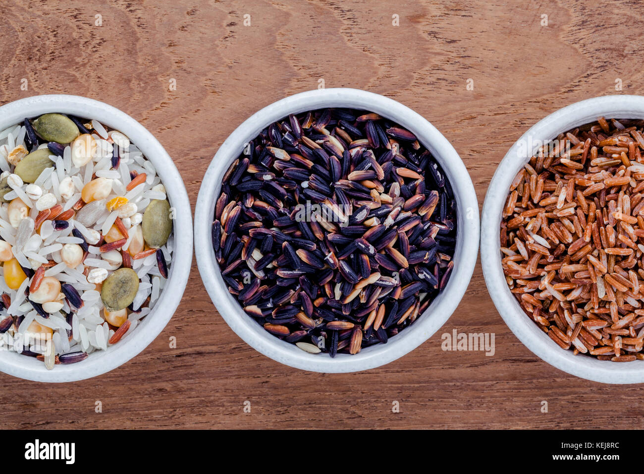 Assortment of traditional thai rice in ceramic bowl on wooden background. The Supper food high Fiber and vitamin - Stock Image