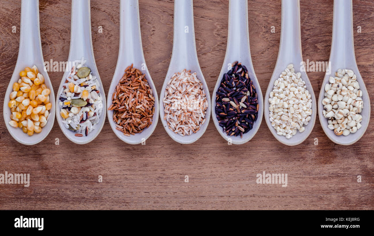 Assortment of traditional thai rice in spoon on wooden background. The Supper food high Fiber and vitamin E for - Stock Image