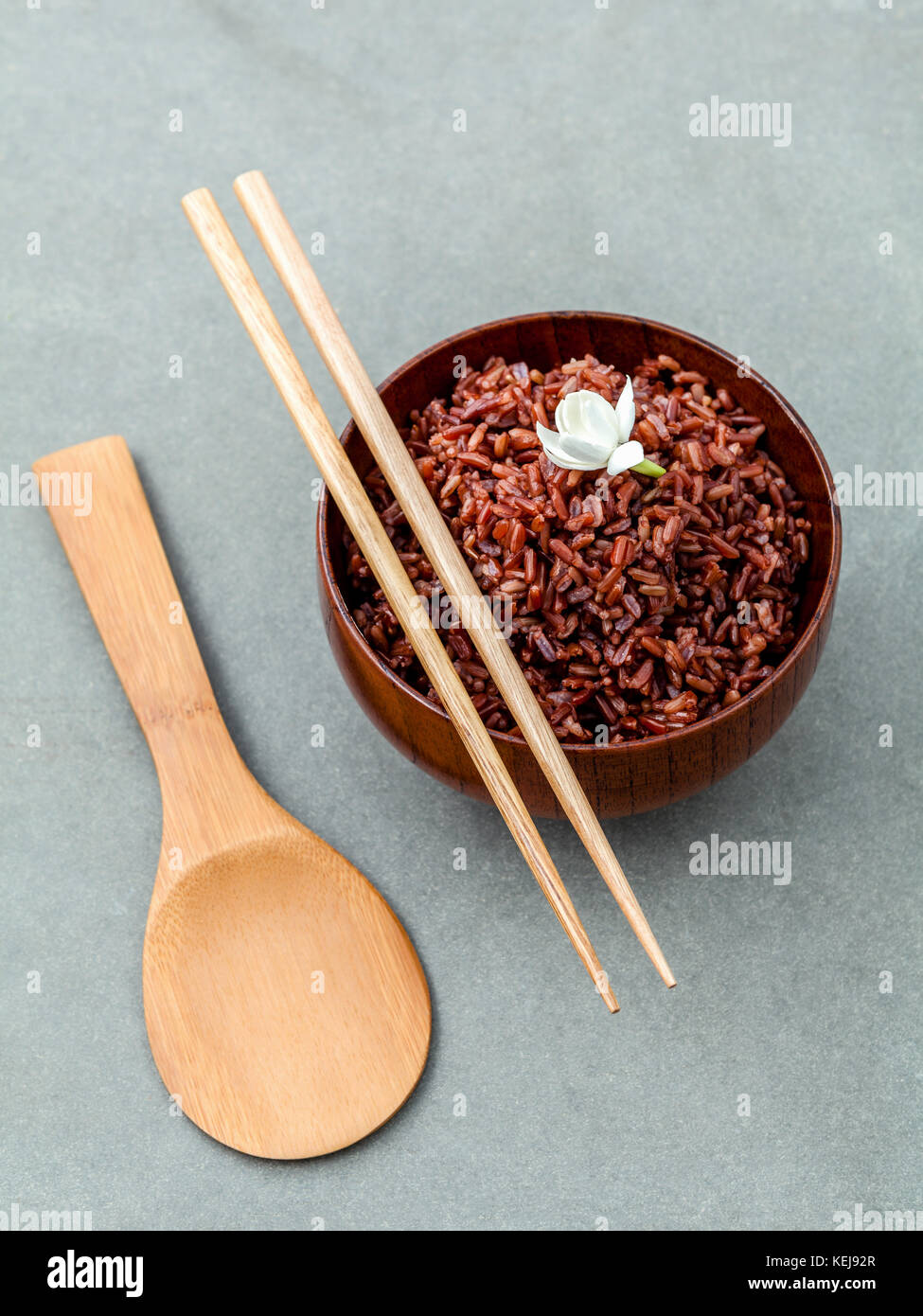 Steamed traditional thai rice in bowl with spoon high fiber and vitamin E for dietary and healthy food. - Stock Image
