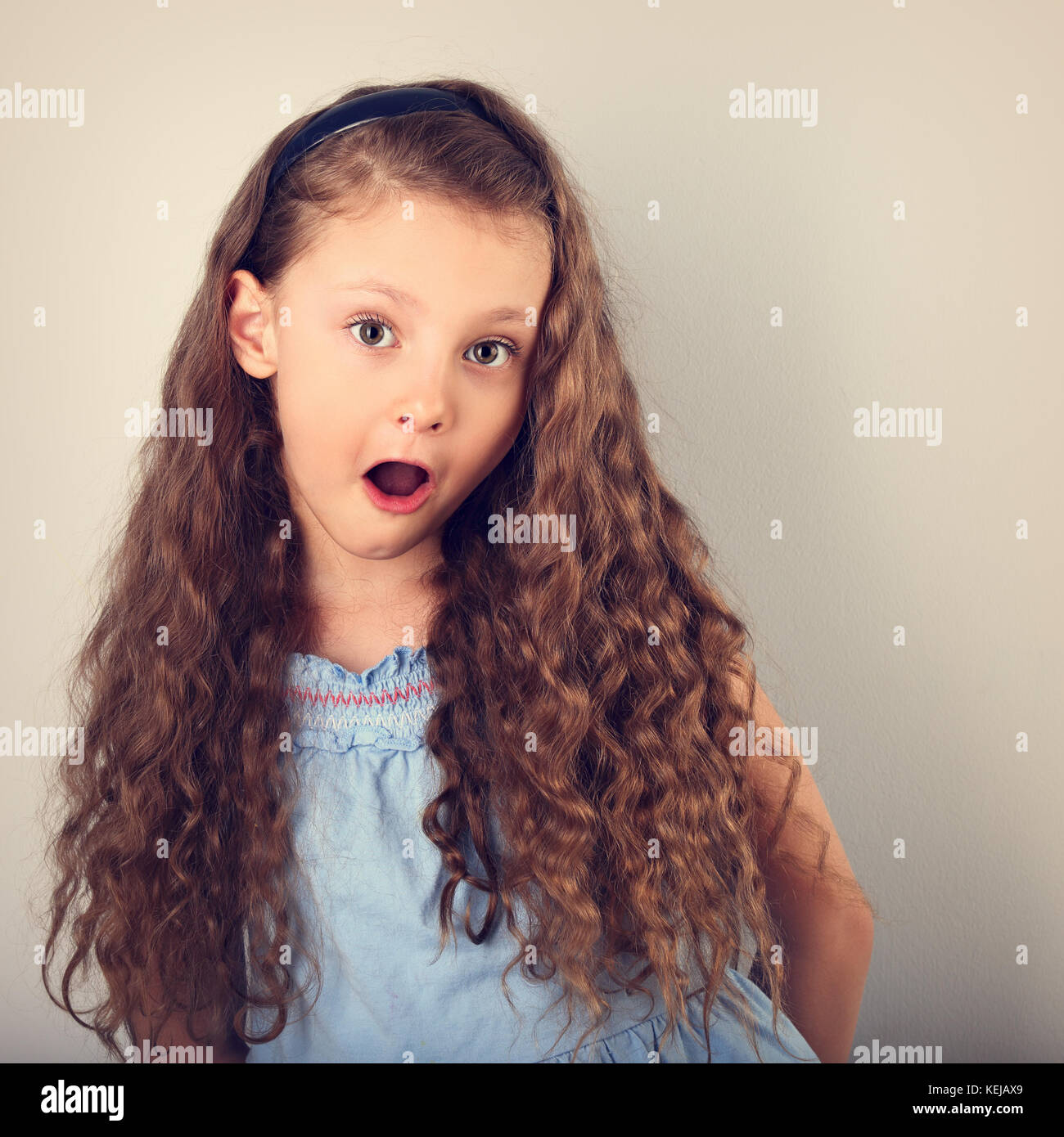 Excited Surprising Kid Girl With Long Curly Hair Style And Wide Open