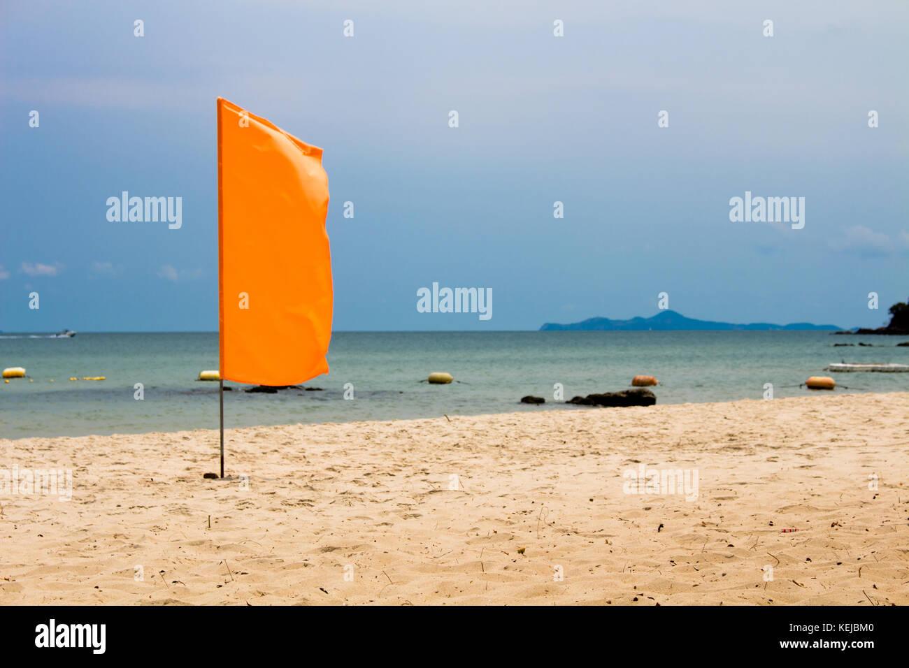 The orange flag on beach, sea background Stock Photo