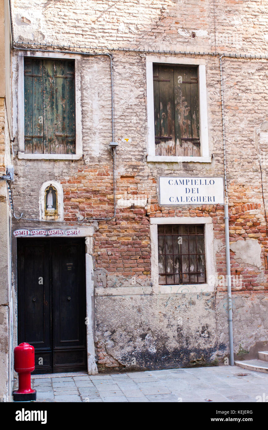 Venice, Italy. Feb 2013: typical venetian houses and flats, with colored walls and gothic window frames. Walls made - Stock Image
