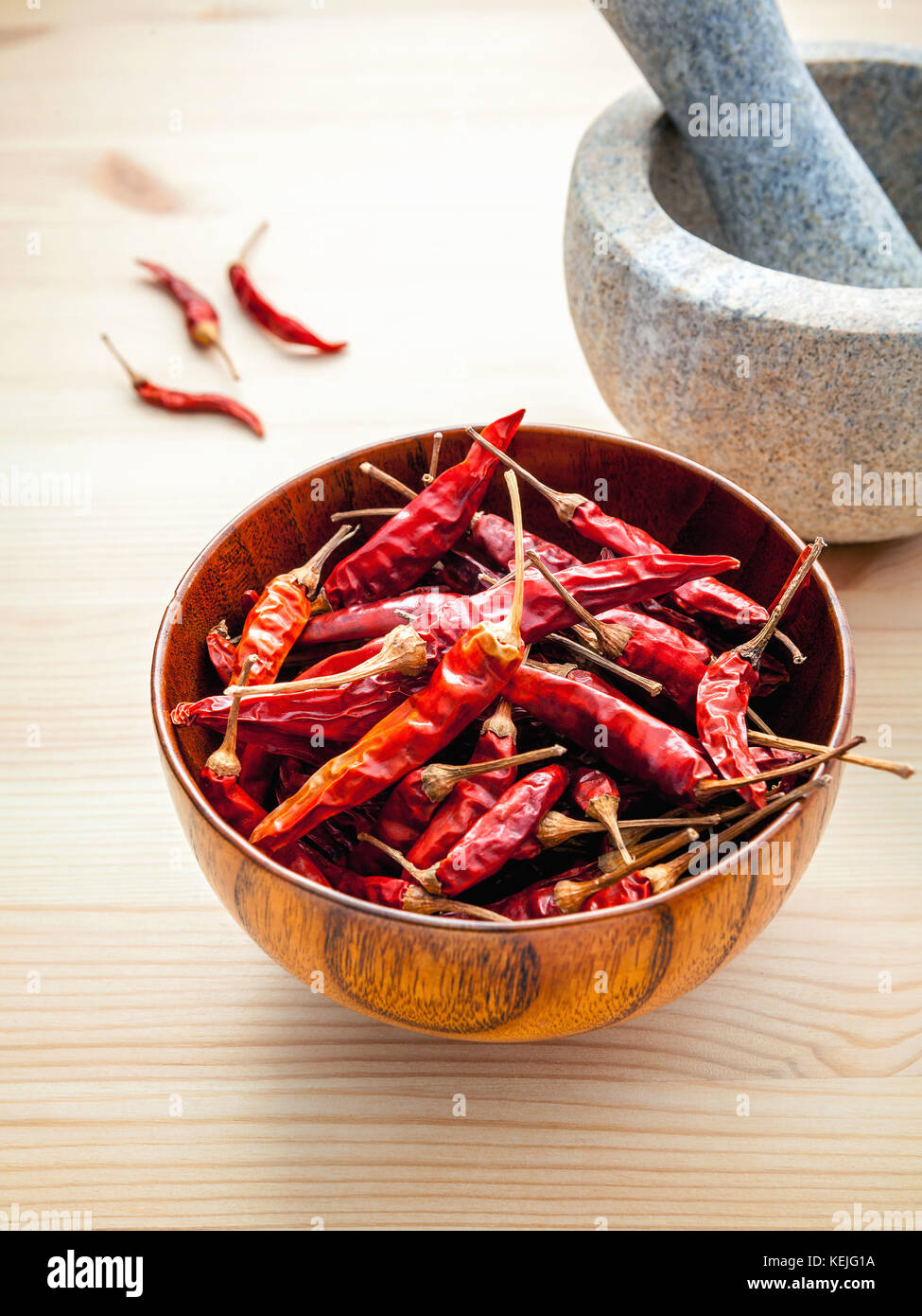 Dried Chillies on white wooden background with mortar and pestle. Selective focus depth of field. - Stock Image