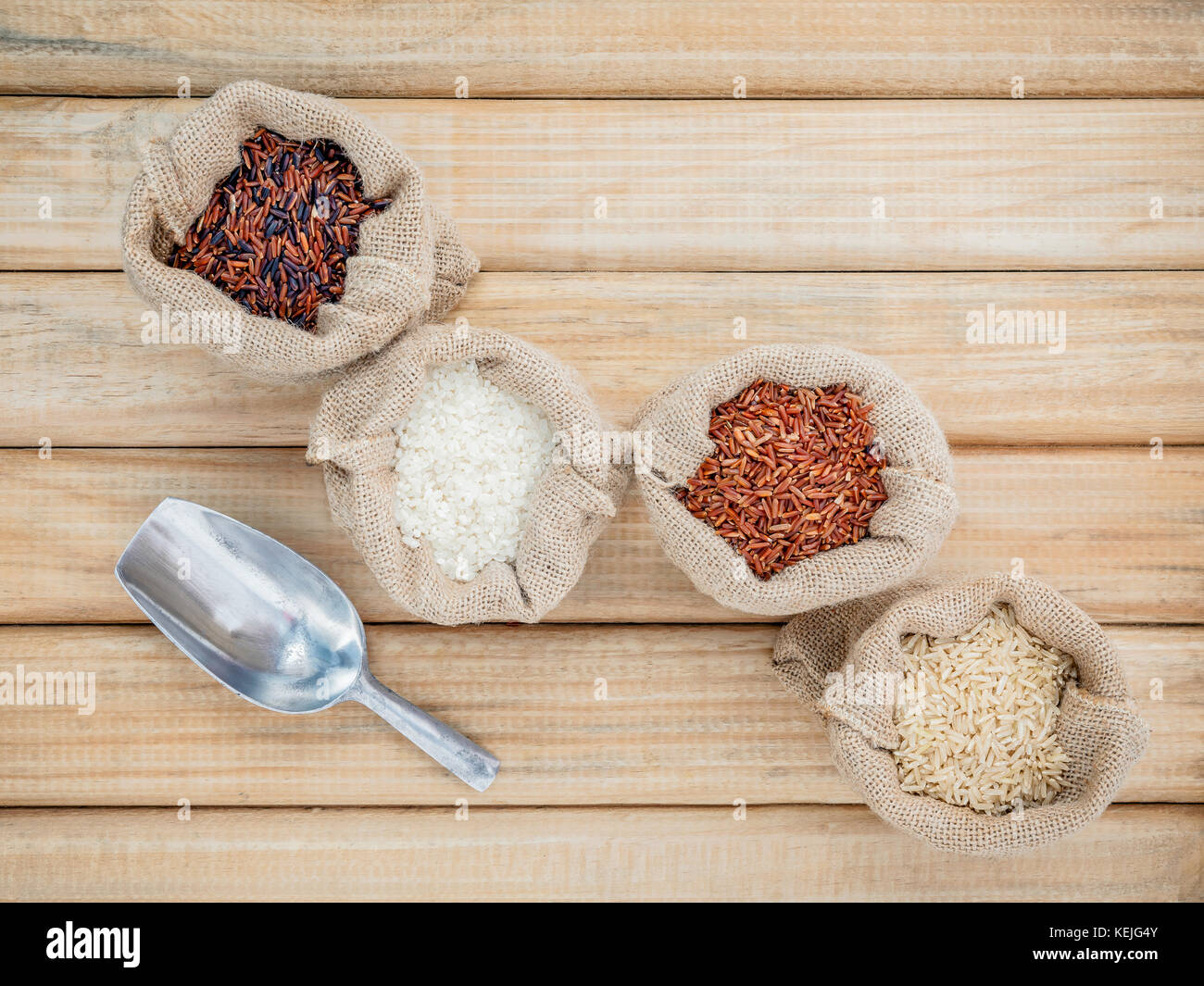 Mixed whole grain traditional thai rices best rices for healthy and super food in hemp sacks bag setup on wooden - Stock Image
