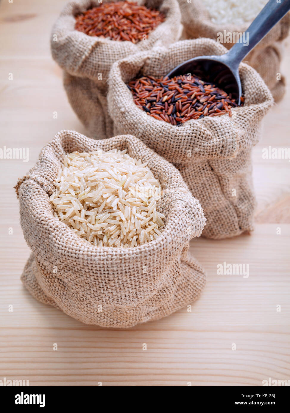 Mixed whole grain traditional thai rices best rices for healthy and super food in hemp sacks bag setup on wooden Stock Photo