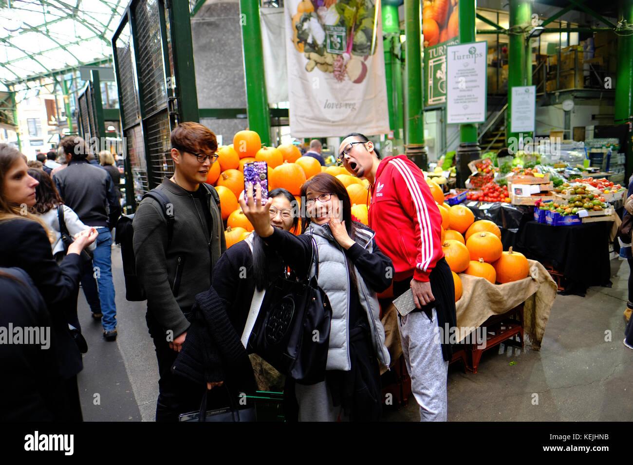 Chinese tourists taking selfie, Borough Market, SE1, London, United Kingdom - Stock Image