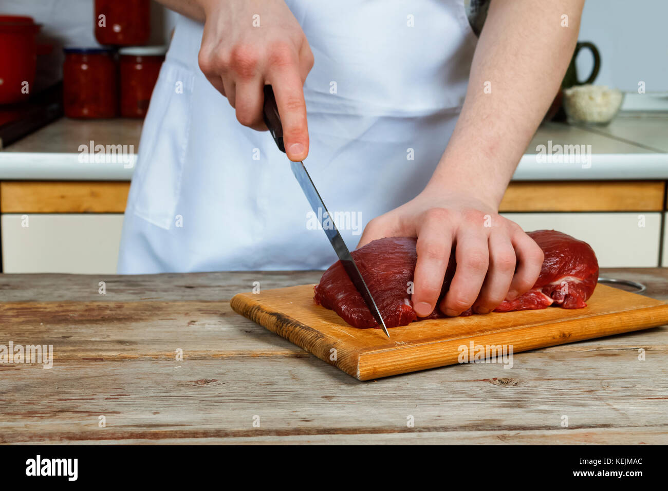 Butcher cutting pork meat on kitchen. man preparation Stock Photo
