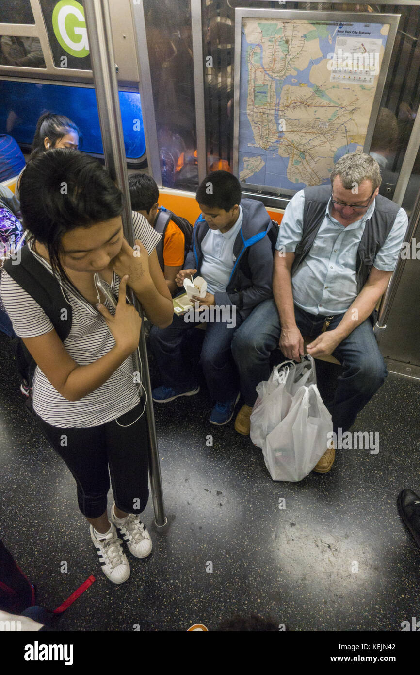 teenage Sian girl stands riding the G train in Brooklyn, NY. - Stock Image
