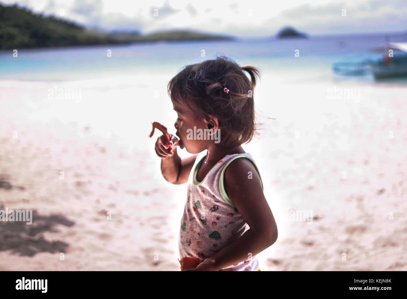 A girl eating papaya on Calaguas beach. - Stock Image