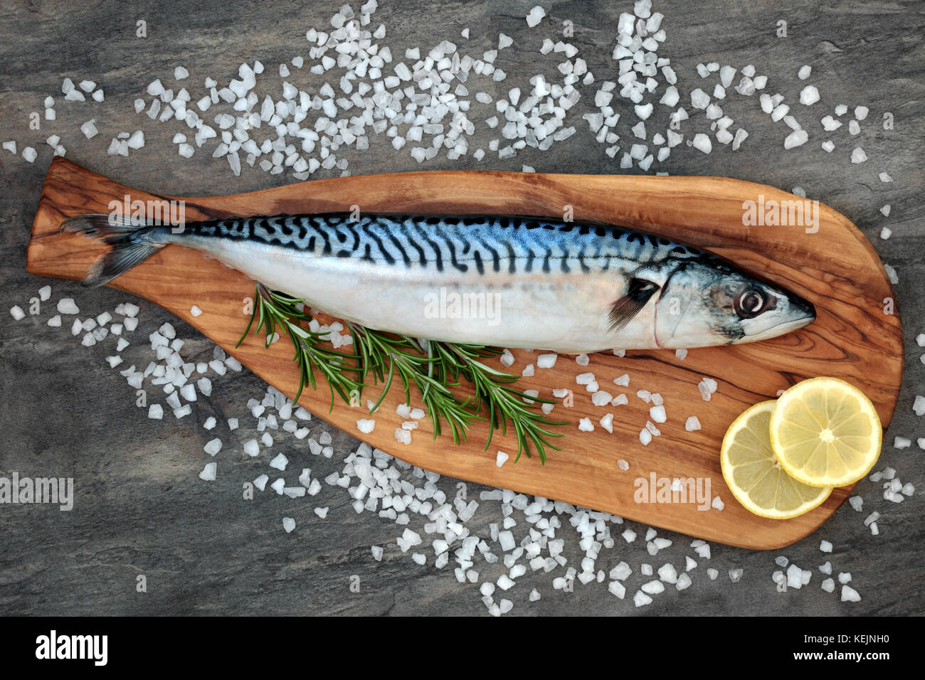 Mackerel fish health food on an olive wood board with course salt, rosemary herb and lemon fruit on marble background. High in omega 3 . Stock Photo