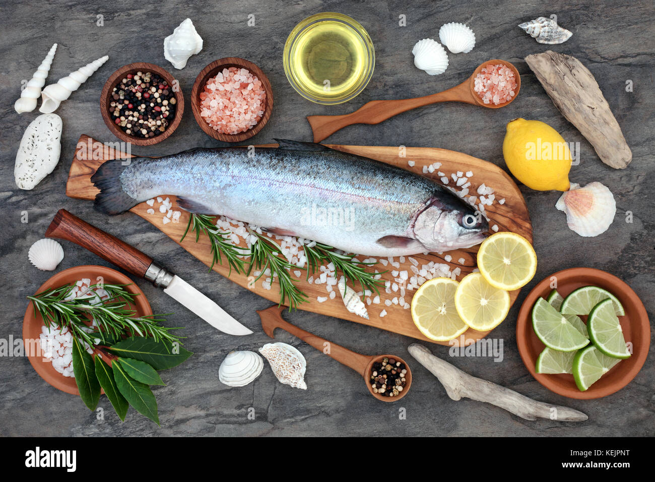 Rainbow trout health food on an olive wood board with seasoning. Very high in omega 3 fatty acid and beneficial - Stock Image
